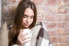 拿着杯子用热的茶的温暖的格子花呢披肩的美丽的妇女 库存图片
