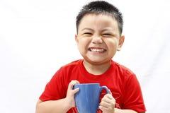 拿着杯子的小男孩 库存照片
