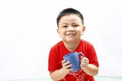 拿着杯子的小男孩 免版税库存照片