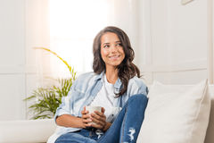 拿着杯子的微笑的少妇,当坐沙发和在家时看  免版税库存照片