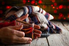 拿着杯子被仔细考虑的酒的手 免版税库存图片