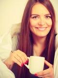 拿着杯子饮料的微笑的妇女在床上 免版税图库摄影