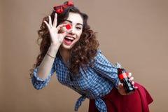 拿着杯子玻璃瓶和给您苏打的女孩的愉快的美丽的别针 妇女在红色衬衣和蓝色格子花呢披肩穿戴了 图库摄影