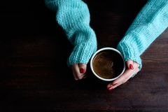 拿着杯子coffe的蓝色毛线衣的女孩递特写镜头 库存照片
