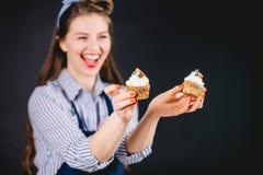 拿着杯形蛋糕和给不同的情感的妇女在手上 健康食物面包店没有糖概念 库存图片