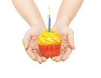 拿着杯形蛋糕的手 免版税库存照片