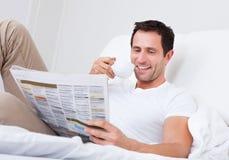 拿着杯手中读取报纸的年轻人 免版税库存图片