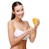 拿着杯橙汁的Attractivesmiling妇女被隔绝在白色 免版税库存图片