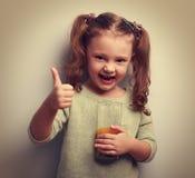 拿着杯汁液的愉快的小女孩 库存照片