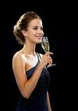 拿着杯汽酒的微笑的妇女 免版税库存图片