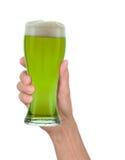 拿着杯泡沫似的绿色啤酒的手 库存图片