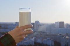 拿着杯牛奶的手 免版税库存照片