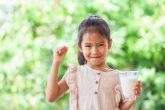拿着杯牛奶的逗人喜爱的亚裔儿童女孩和做强的姿态 免版税库存照片