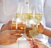 拿着杯白葡萄酒的人们做多士 库存照片