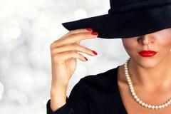 拿着杯白葡萄酒的可爱的妇女 戴黑帽会议的一个美丽的女孩的画象 免版税库存照片
