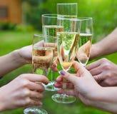 拿着杯香槟的人们做多士户外 免版税库存图片