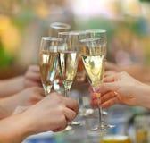 拿着杯香槟的人们做多士 库存照片