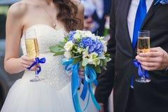 拿着杯香槟的新娘和新郎 免版税库存图片