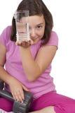 拿着杯水和重量的十几岁的女孩 免版税库存图片