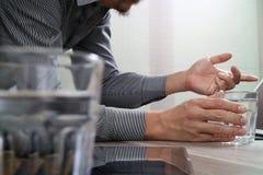 拿着杯水的网站设计师运转数字式片剂a 图库摄影