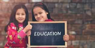 拿着板岩板的两个一点印度农村女孩 免版税库存照片