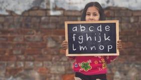 拿着板岩板的印度农村女孩 免版税图库摄影
