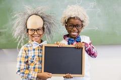 拿着板岩的两个微笑的学校孩子画象在教室 免版税库存照片