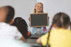 拿着板岩的愉快的白种人女小学生在教室在有代替他的同学的学校 库存图片