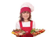 拿着板材用三文鱼海鲜的小女孩厨师 免版税库存照片