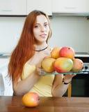 拿着板材用芒果的普通的长发妇女 库存照片