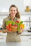 拿着板材的愉快的主妇有很多菜在厨房里 免版税库存图片