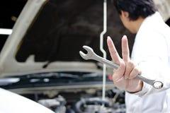 拿着板钳和举它的确信的年轻技工的手两个手指是展示战斗与工作反对在开放敞篷的汽车在 免版税库存照片