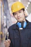 拿着板钳和穿安全帽的年轻工程师画象 免版税库存图片
