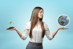 拿着极少数与植物的土壤的妇女在一手和地球上在其他 免版税图库摄影