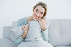 拿着枕头的平安的白肤金发的妇女坐长沙发 库存照片