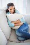 拿着枕头的快乐的妇女坐长沙发 库存照片