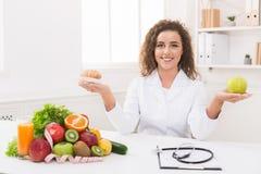 拿着果子和新月形面包在手上的妇女营养师 免版税库存照片