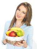 拿着果子的篮子年轻美丽的健康妇女 免版税库存照片