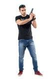 拿着枪用两只手的简单的衣裳的严肃的谨慎警察 免版税库存照片
