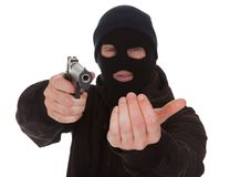 拿着枪的夜贼佩带的面具 免版税图库摄影