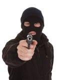 拿着枪的夜贼佩带的面具 免版税库存照片