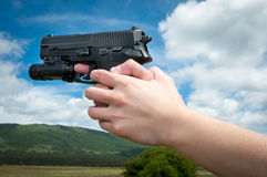 拿着枪的妇女的手,  免版税库存图片