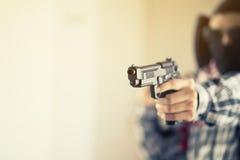 拿着枪的恐怖分子的手 免版税库存图片