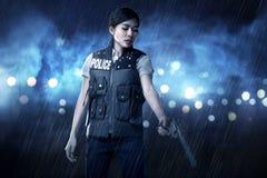 拿着枪的美丽的警察妇女 免版税库存照片