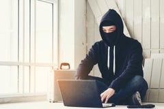 拿着枪研究他的计算机,战争,恐怖主义, ter的黑客 免版税库存图片