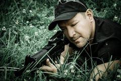 拿着枪k44和射击在下午的人,对目标靠着在绿草,小深度 免版税库存图片