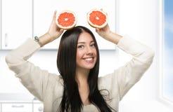 拿着柑橘的滑稽的女孩在厨房里 免版税库存照片