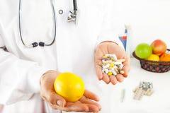 拿着柠檬和药片的医生 免版税库存照片