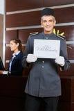拿着标志的微笑的旅馆看门人 库存图片