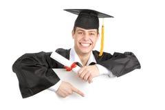 拿着标志的微笑的男性毕业生 免版税库存图片